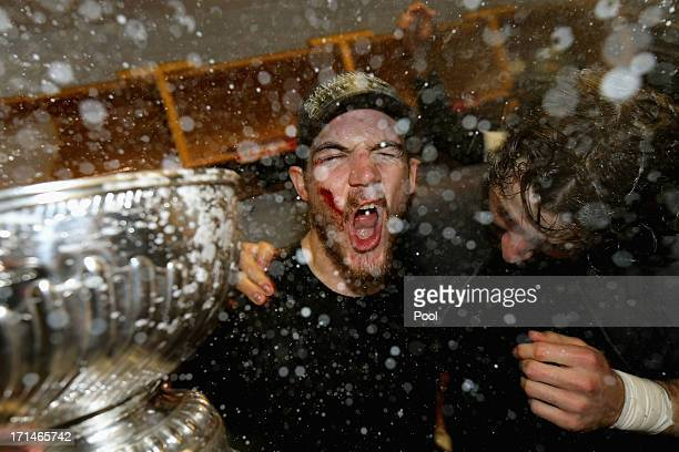 Andrew Shaw of the Chicago Blackhawks celebrates with the Stanley Cup in the locker room after defeating the Boston Bruins in Game Six of the 2013...