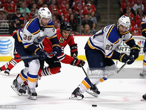Andrew Shaw of the Chicago Blackhawks chases the puck between Troy Brouwer and Alex Pietrangelo of the St Louis Blues in Game Three of the Western...