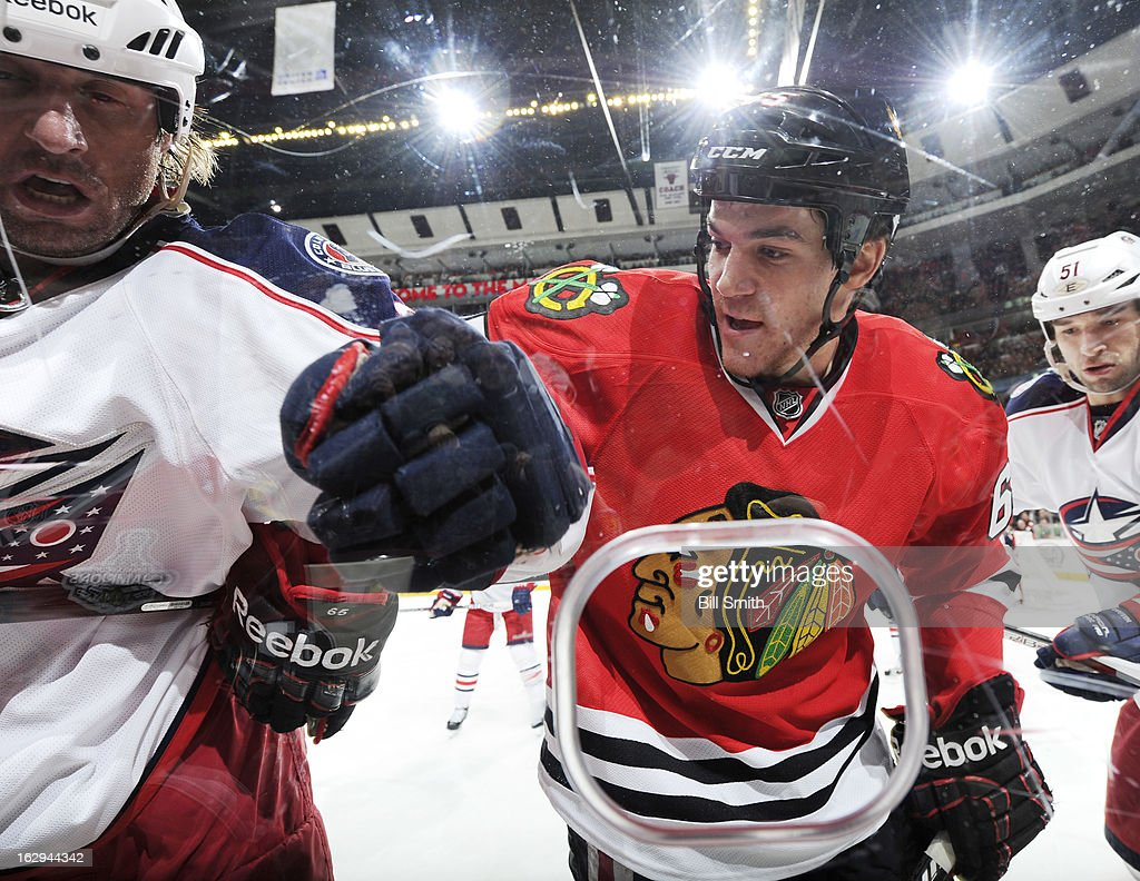 Andrew Shaw #65 of the Chicago Blackhawks checks a Columbus Blue Jackets player during the NHL game on March 01, 2013 at the United Center in Chicago, Illinois. The Chicago Blackhawks defeated the Columbus Blue Jackets 4-3 in overtime.