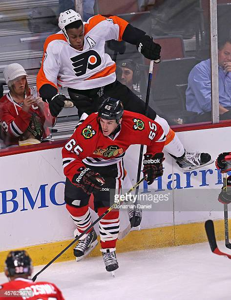 Andrew Shaw of the Chicago Blackhawks checks Wayne Simmonds of the Philadelphia Flyers at the United Center on October 21 2014 in Chicago Illinois...