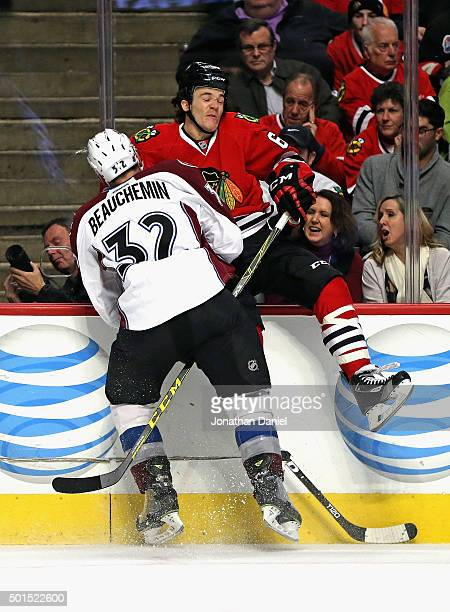 Andrew Shaw of the Chicago Blackhawks collides against the boards with Francois Beauchemin of the Colorado Avalanche at the United Center on December...