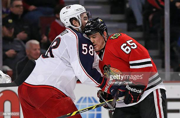 Andrew Shaw of the Chicago Blackhawks collides with David Savard of the Columbus Blue Jackets at the United Center on March 27 2015 in Chicago...