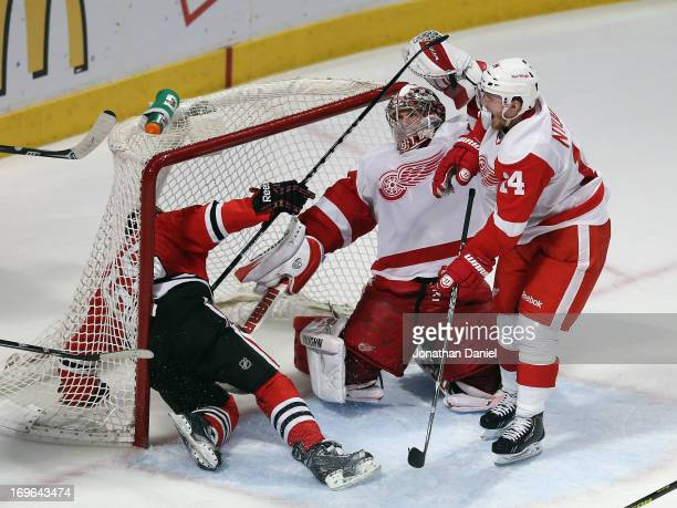 Andrew Shaw of the Chicago Blackhawks falls into the net after colliding with Jimmy Howard and Damien Brunner of the Detroit Red Wings in Game Seven...
