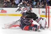 Andrew Shaw of the Chicago Blackhawks falls over goaltender Corey Crawford of the Chicago Blackhawks and Nick Foligno of the Columbus Blue Jackets...