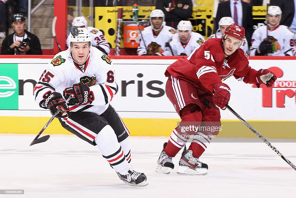 Andrew Shaw #65 of the Chicago Blackhawks flips up the puck past <a gi-track='captionPersonalityLinkClicked' href=/galleries/search?phrase=Antoine+Vermette&family=editorial&specificpeople=206302 ng-click='$event.stopPropagation()'>Antoine Vermette</a> #50 of the Phoenix Coyotes during the NHL game at Jobing.com Arena on January 20, 2013 in Glendale, Arizona. The Blackhawks defeated the Coyotes 6-4.