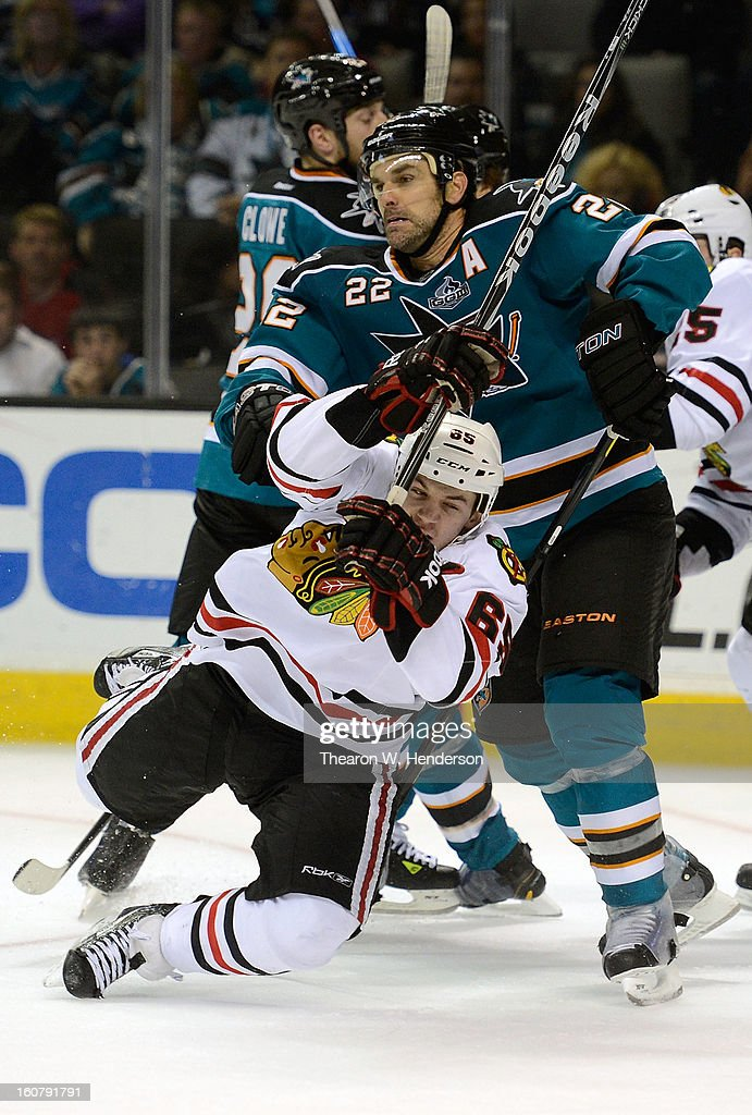 Andrew Shaw #65 of the Chicago Blackhawks gets checked to the ice by Dan Boyle #22 of the San Jose Sharks in the third period at HP Pavilion on February 5, 2013 in San Jose, California. The Blackhawks won the game 5-3.
