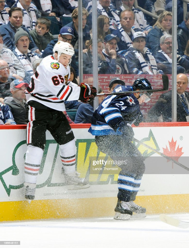 Andrew Shaw #65 of the Chicago Blackhawks hits the glass as he misses a check on <a gi-track='captionPersonalityLinkClicked' href=/galleries/search?phrase=Grant+Clitsome&family=editorial&specificpeople=4596638 ng-click='$event.stopPropagation()'>Grant Clitsome</a> #24 of the Winnipeg Jets during third period action at the MTS Centre on November 2, 2013 in Winnipeg, Manitoba, Canada.