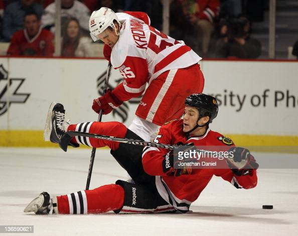 Andrew Shaw of the Chicago Blackhawks hits the ice while battling with Niklas Kronwall of the Detroit Red Wings at the United Center on January 8...