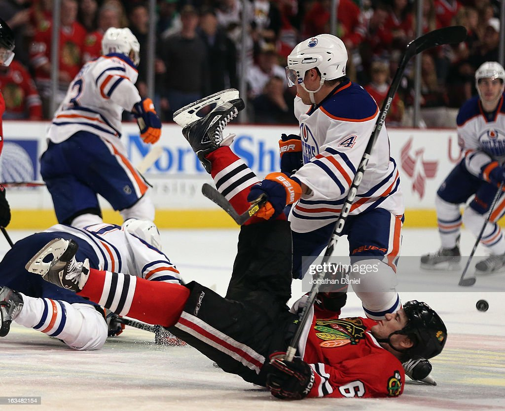 Andrew Shaw #65 of the Chicago Blackhawks is dumped to the ice by Taylor Hall #4 of the Edmonton Oilers at the United Center on March 10, 2013 in Chicago, Illinois.
