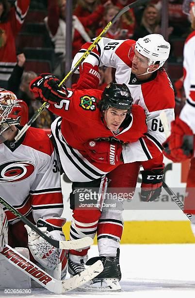 Andrew Shaw of the Chicago Blackhawks is grabbed in front of the goal by Ron Hainsey of the Carolina Hurricanes at the United Center on December 27...