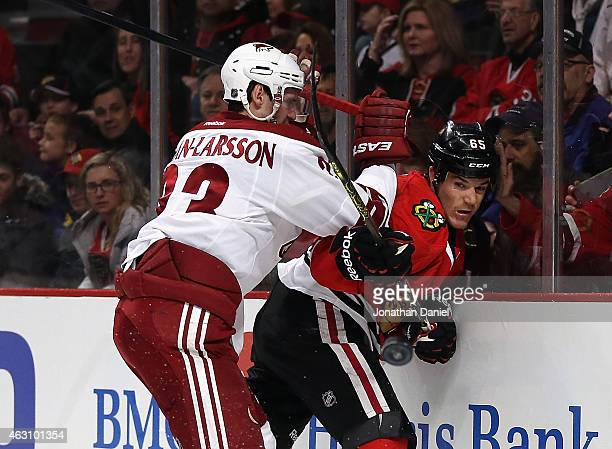 Andrew Shaw of the Chicago Blackhawks is hit in the back by Oliver EkmanLarsson of the Arizona Coyotes as he passes the puck at the United Center on...