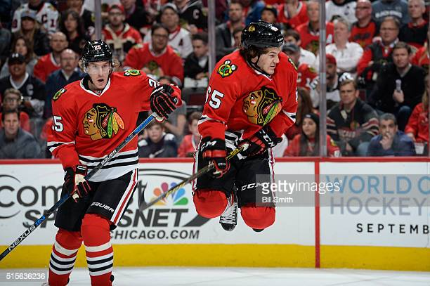 Andrew Shaw of the Chicago Blackhawks jumps out of the way of the puck as teammate Dale Weise watches behind in the first period of the NHL game...
