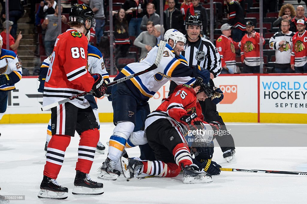 Andrew Shaw #65 of the Chicago Blackhawks lands on Alexander Steen #20 of the St. Louis Blues as Troy Brouwer #36 pushes behind in the third period of Game Four of the Western Conference First Round during the 2016 NHL Stanley Cup Playoffs at the United Center on April 19, 2016 in Chicago, Illinois.