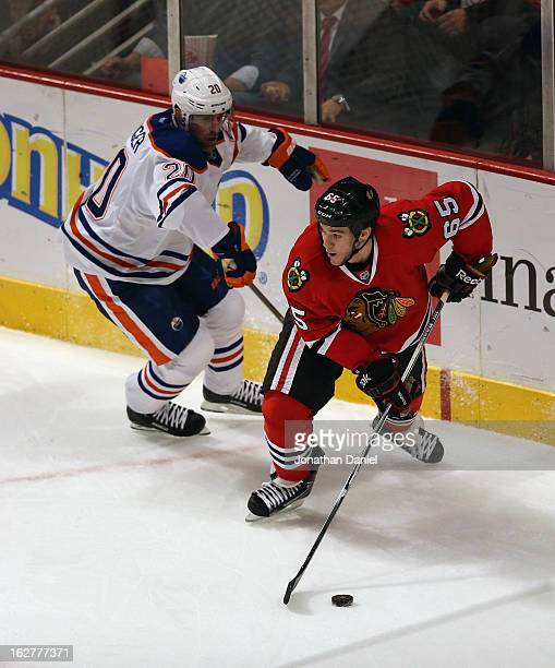 Andrew Shaw of the Chicago Blackhawks looks to pass under pressure from Eric Belanger of the Edmonton Oilers at the United Center on February 25 2013...