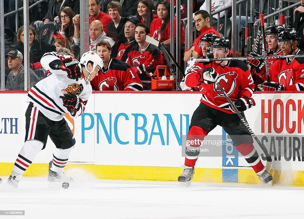 Andrew Shaw #65 of the Chicago Blackhawks loses his stick after being checked by Matt Taormina #32 of the New Jersey Devils during the game at the Prudential Center on March 27, 2012 in Newark, New Jersey.
