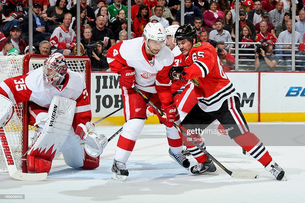 Andrew Shaw #65 of the Chicago Blackhawks pushes into Jakub Kindl #4 of the Detroit Red Wings, next to goalie Jimmy Howard #35 of the Red Wings, in Game Two of the Western Conference Semifinals during the 2013 Stanley Cup Playoffs at the United Center on May 18, 2013 in Chicago, Illinois.