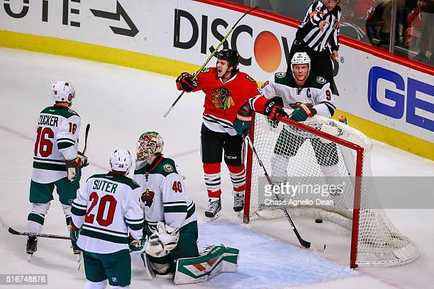 Andrew Shaw of the Chicago Blackhawks reacts after scoring on goalie Devan Dubnyk of the Minnesota Wild as Mikko Koivu stands behind in the second...