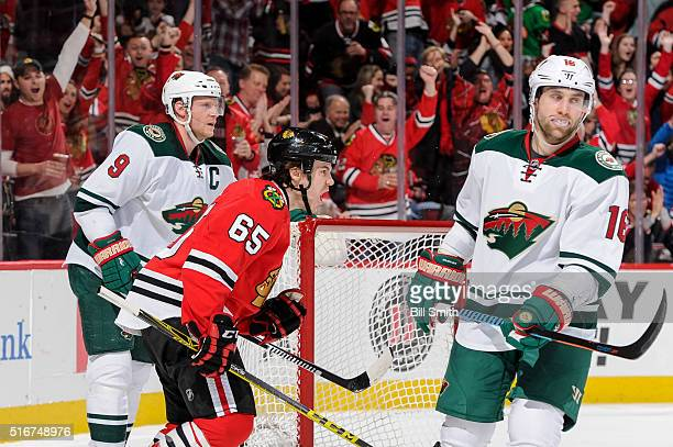 Andrew Shaw of the Chicago Blackhawks reacts in between Mikko Koivu and Jason Zucker of the Minnesota Wild after scoring in the second period of the...