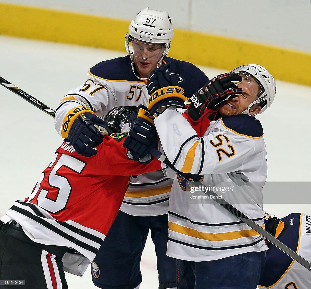 Andrew Shaw #65 of the Chicago Blackhawks shoves <a gi-track='captionPersonalityLinkClicked' href=/galleries/search?phrase=Alexander+Sulzer&family=editorial&specificpeople=673531 ng-click='$event.stopPropagation()'>Alexander Sulzer</a> #52 of the Buffalo Sabres in the face as Tyler Meyers #57 tries to break it up at the United Center on October 12, 2013 in Chicago, Illinois.