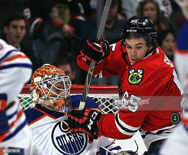 Andrew Shaw of the Chicago Blackhawks tangles with Cam Talbot of the Edmonton Oilers as the puck flys off of Talbots' chest at the United Center on...