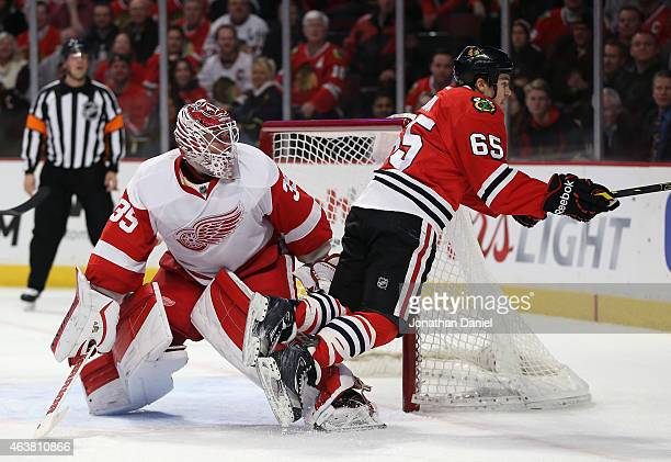 Andrew Shaw of the Chicago Blackhawks trips over Jimmy Howard of the Detroit Red Wings at the United Center on February 18 2015 in Chicago Illinois