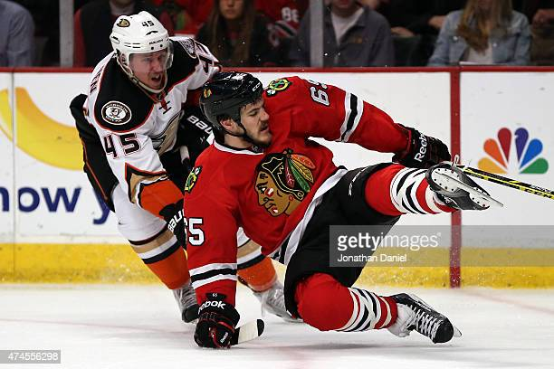 Andrew Shaw of the Chicago Blackhawks trips while going for a puck against Sami Vatanen of the Anaheim Ducks in the second period of Game Four of the...