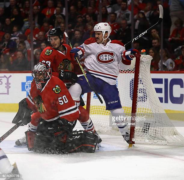 Andrew Shaw of the Montreal Canadiens is shoved in the goal by Ryan Hartman of the Chicago Blackhawks behind Corey Crawford at the United Center on...