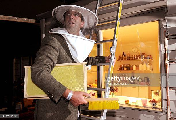 Andrew Short an amateur beekeeper stands on a ladder at the back of his house a day after he was stung 60 times by his bees in a failed attempt to...