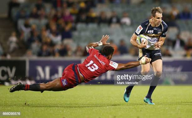 Andrew Smith of the Brumbies evades the tackle of Samu Kerevi of the Reds during the round seven Super Rugby match between the Brumbies and the Reds...