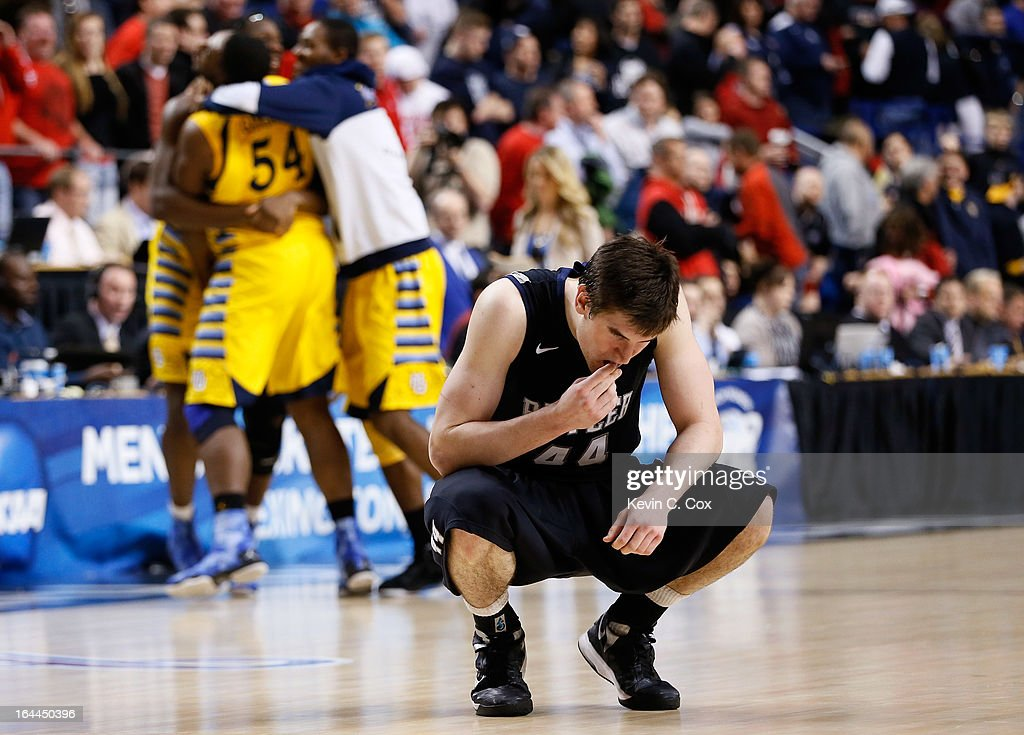 Andrew Smith #44 of the Butler Bulldogs reacts as the Marquette Golden Eagles celebrate after defeating the Bulldogs during the third round of the 2013 NCAA Men's Basketball Tournament at Rupp Arena on March 23, 2013 in Lexington, Kentucky.