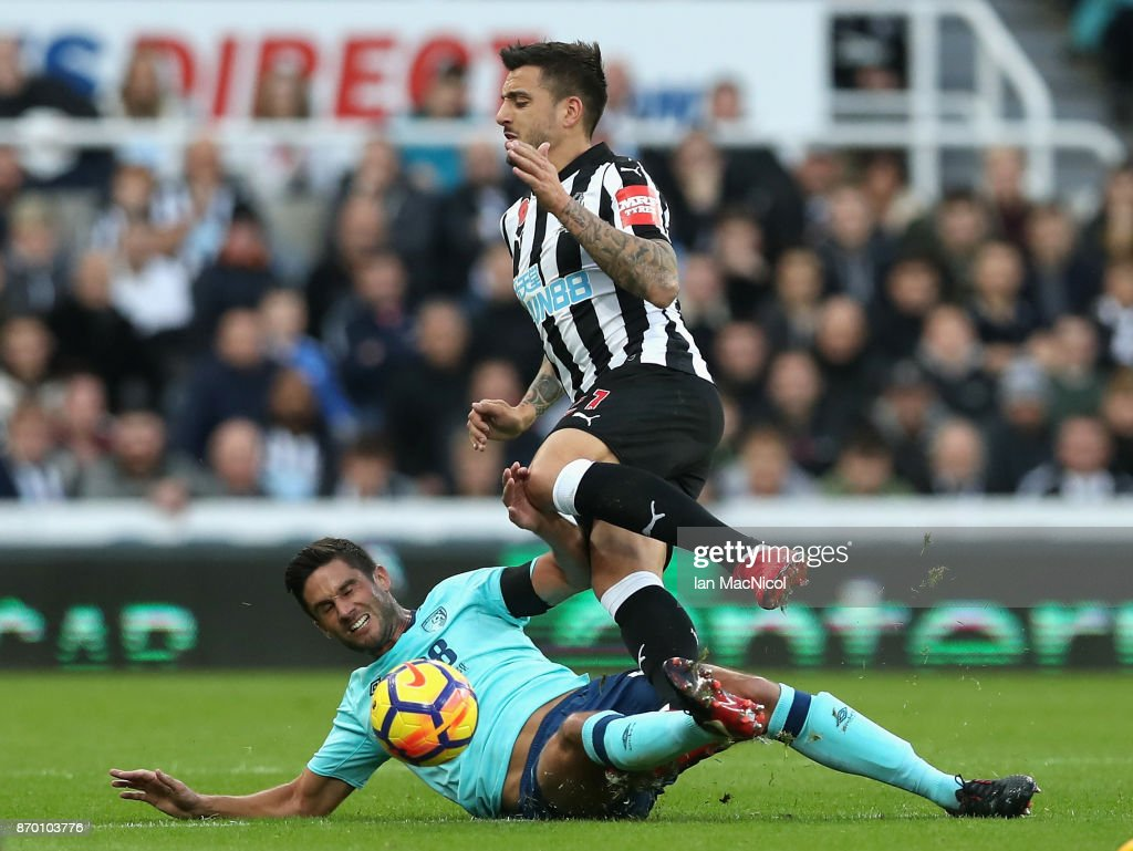Andrew Surman of AFC Bournemouth tackles Joselu of Newcastle United during the Premier League match between Newcastle United and AFC Bournemouth at St. James Park on November 4, 2017 in Newcastle upon Tyne, England.