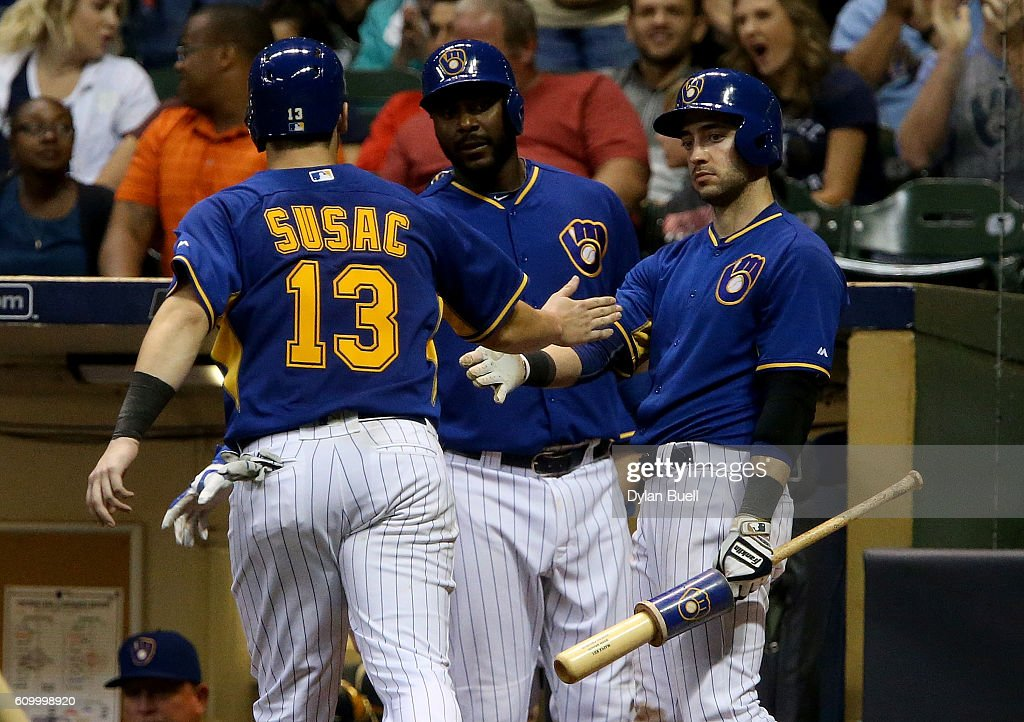 Andrew Susac #13 of the Milwaukee Brewers is congratulated by teammates Ryan Braun #8 and Chris Carter #33 after scoring a run in the seventh inning against the Cincinnati Reds at Miller Park on September 23, 2016 in Milwaukee, Wisconsin.
