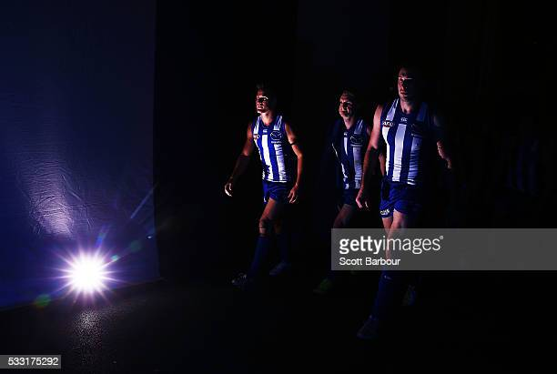 Andrew Swallow Jack Ziebell and Todd Goldstein of the Kangaroos lead their players onto the field during the round nine AFL match between the North...