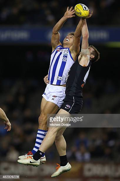 Andrew Swallow of the Kangaroos competes for the ball against Tom Bell of the Blues during the round 18 AFL match between the Carlton Blues and the...