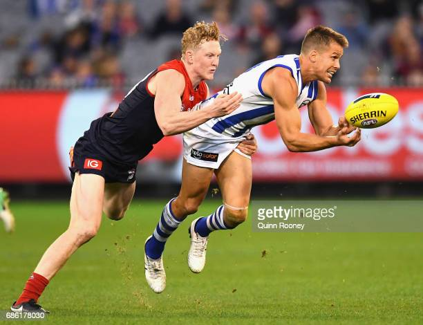Andrew Swallow of the Kangaroos handballs whilst being tackled by Clayton Oliver of the Demons during the round nine AFL match between the Melbourne...