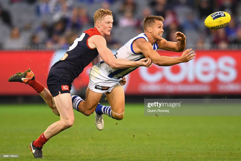 Andrew Swallow of the Kangaroos handballs whilst being tackled by Clayton Oliver of the Demons during the round nine AFL match between the Melbourne Demons and the North Melbourne Kangaroos at Melbourne Cricket Ground on May 21, 2017 in Melbourne, Australia.