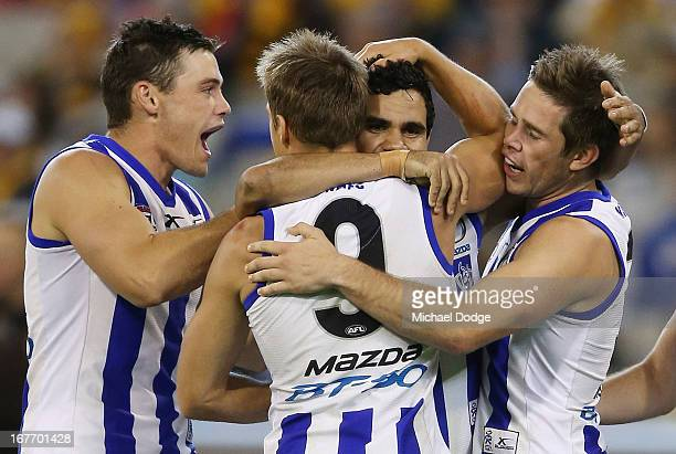 Andrew Swallow of the Kangaroos hugs Lindsay Thomas who kicked a goal as teamates Nathan Grima and Ryan Bastinac come in during the round five AFL...
