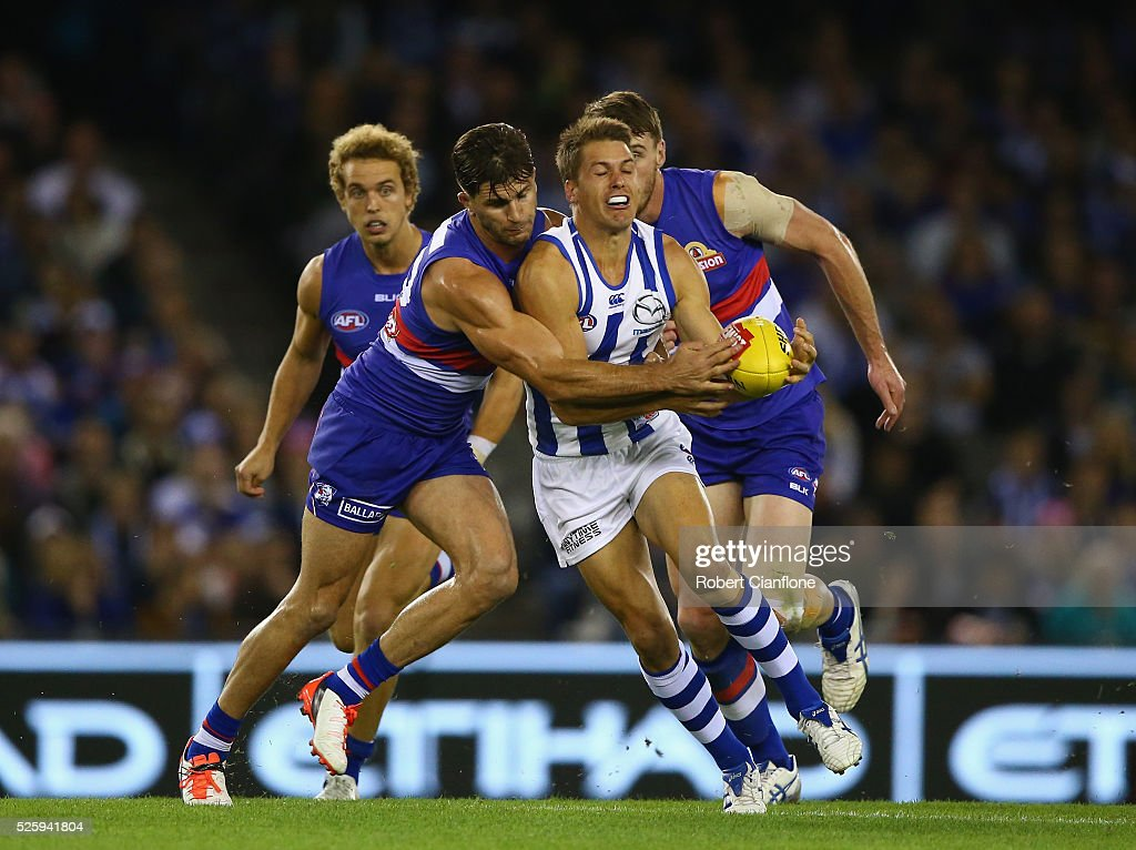 <a gi-track='captionPersonalityLinkClicked' href=/galleries/search?phrase=Andrew+Swallow&family=editorial&specificpeople=608525 ng-click='$event.stopPropagation()'>Andrew Swallow</a> of the Kangaroos is challenged by Koby Stevens of the Bulldogs during the round six AFL match between the North Melbourne Kangaroos and the Western Bulldogs at Etihad Stadium on April 29, 2016 in Melbourne, Australia.