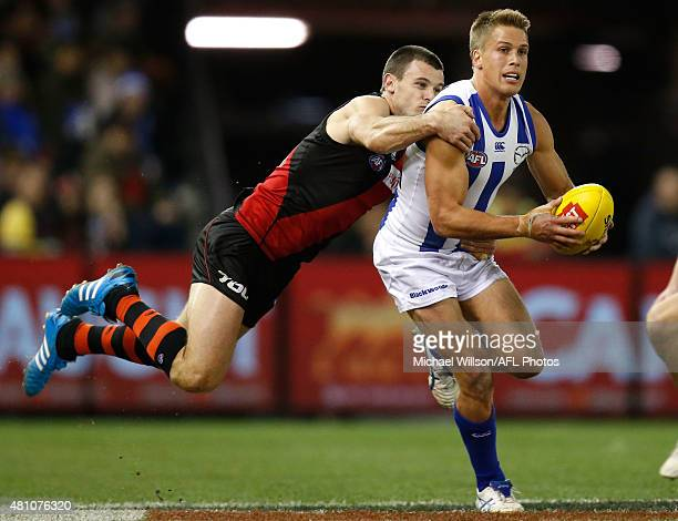 Andrew Swallow of the Kangaroos is tackled by Brent Stanton of the Bombers during the 2015 AFL round 16 match between the North Melbourne Kangaroos...