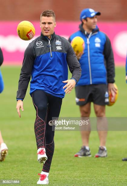 Andrew Swallow of the Kangaroos kicks the ball as Brad Scott coach of the Kangaroos looks on during a North Melbourne Kangaroos AFL training session...