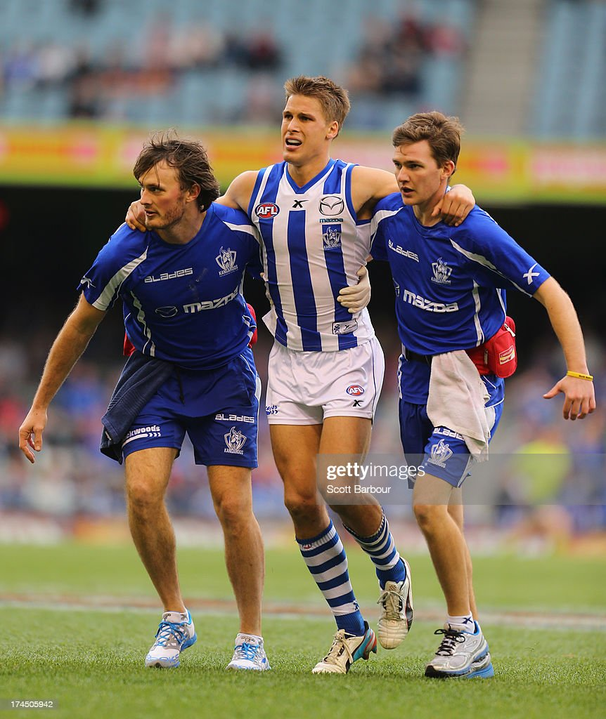 <a gi-track='captionPersonalityLinkClicked' href=/galleries/search?phrase=Andrew+Swallow&family=editorial&specificpeople=608525 ng-click='$event.stopPropagation()'>Andrew Swallow</a> of the Kangaroos leaves the field injured during the round 18 AFL match between the Melbourne Demons and the North Melbourne Kangaroos at Etihad Stadium on July 27, 2013 in Melbourne, Australia.