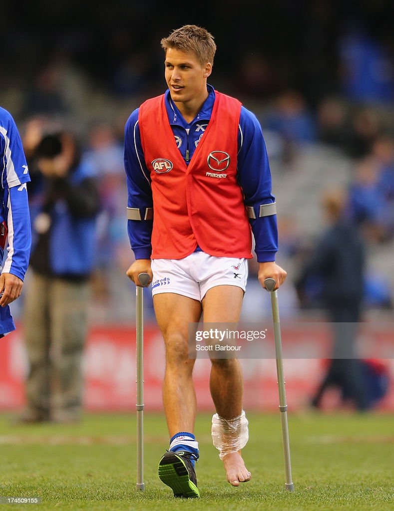 Andrew Swallow of the Kangaroos leaves the field on crutches during the round 18 AFL match between the Melbourne Demons and the North Melbourne Kangaroos at Etihad Stadium on July 27, 2013 in Melbourne, Australia.