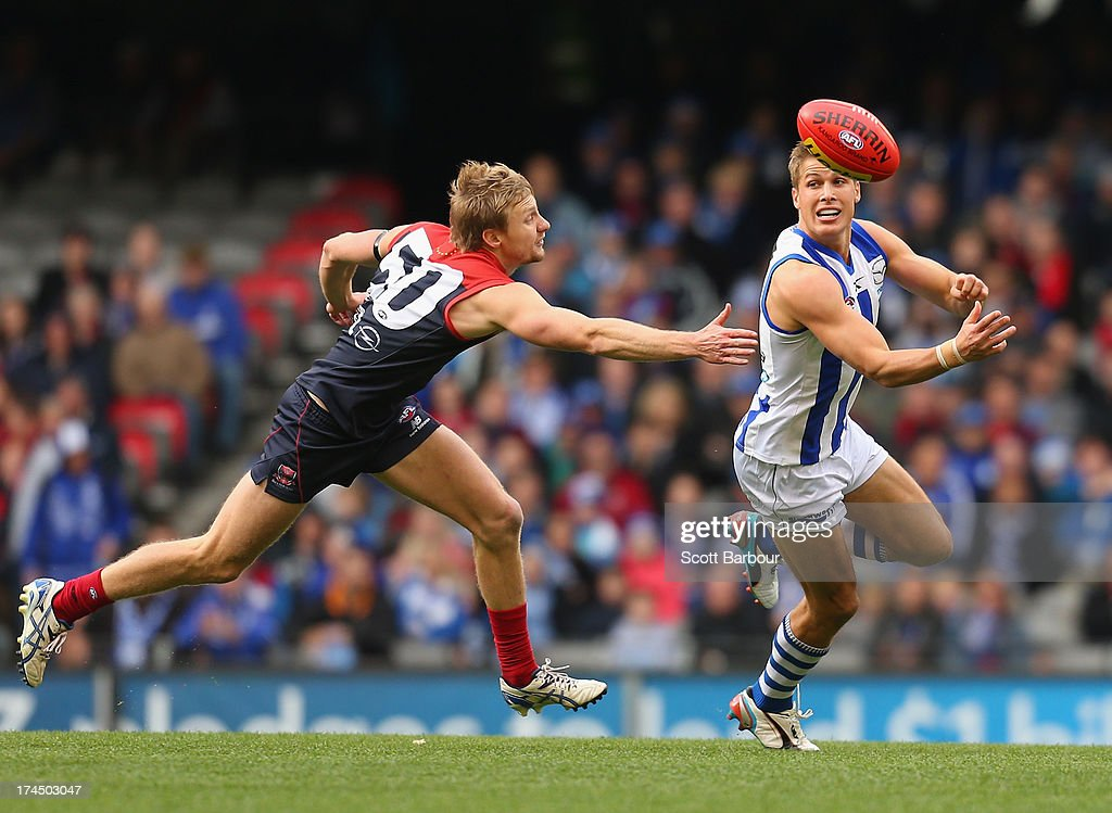 Andrew Swallow of the Kangaroos passes the ball as Mitchell Clisby of the Demons defends during the round 18 AFL match between the Melbourne Demons and the North Melbourne Kangaroos at Etihad Stadium on July 27, 2013 in Melbourne, Australia.
