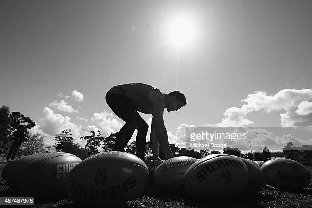 Andrew Swallow of the Kangaroos picks up a ball to use during a North Melbourne Kangaroos AFL training session at Arden Street Ground on September 10...