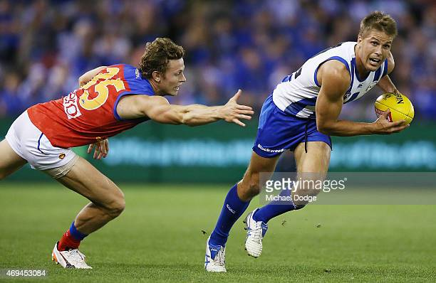Andrew Swallow of the Kangaroos runs with the ball away Ryan Lester of the Lions during the round two AFL match between the North Melbourne Kangaroos...