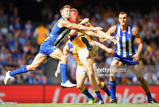 Andrew Swallow of the Kangaroos smouthers a kick by Drew Petrie of the Eagles during the round one AFL match between the North Melbourne Kangaroos...
