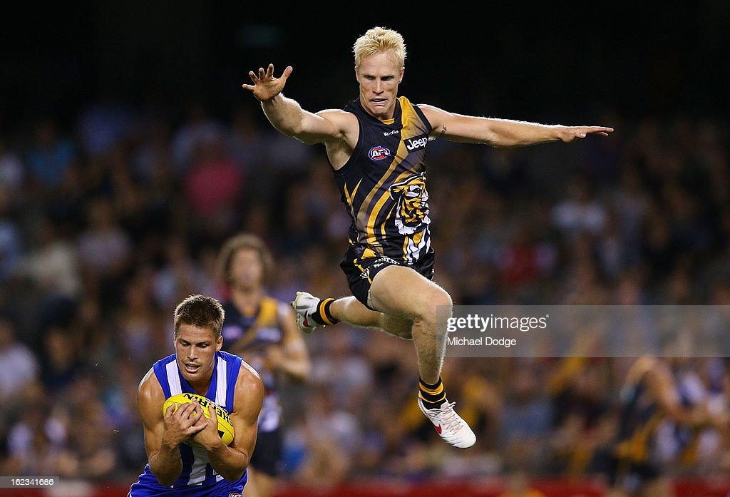 <a gi-track='captionPersonalityLinkClicked' href=/galleries/search?phrase=Andrew+Swallow&family=editorial&specificpeople=608525 ng-click='$event.stopPropagation()'>Andrew Swallow</a> of the North Melbourne Kangaroos marks the ball against Steven Morris of the Richmond Tigers during the round one AFL NAB Cup match between the Richmond Tigers and the North Melbourne Kangaroos at Etihad Stadium on February 22, 2013 in Melbourne, Australia.