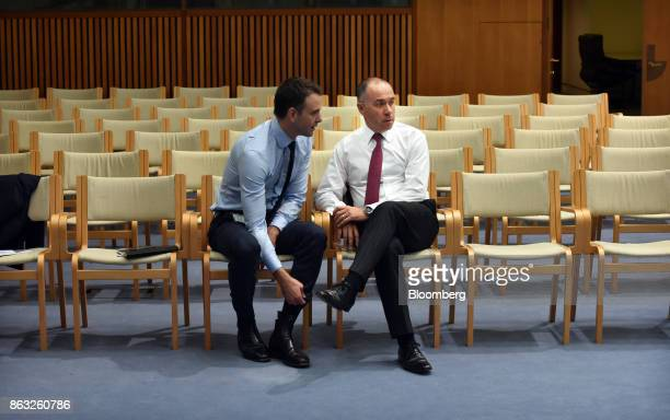 Andrew Thorburn chief executive officer of National Australia Bank Ltd right speaks to a colleague during a hearing before the House of...