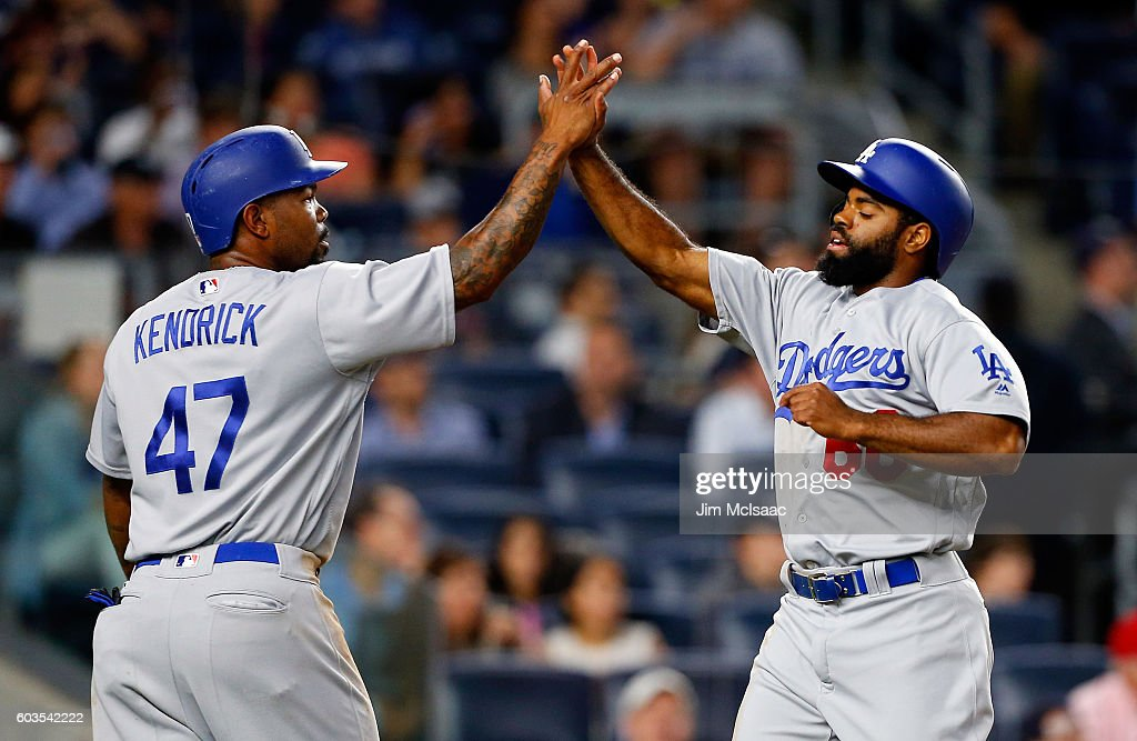 Andrew Toles #60 and Howie Kendrick #47 of the Los Angeles Dodgers reacts after scoring in the second inning against the New York Yankees at Yankee Stadium on September 12, 2016 in the Bronx borough of New York City.