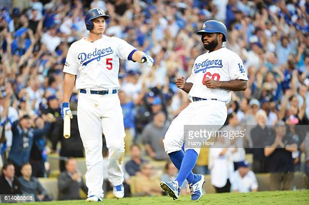 Andrew Toles of the Los Angeles Dodgers celebrates with Corey Seager after scoring on a single by Chase Utley in the eighth inning during game four...